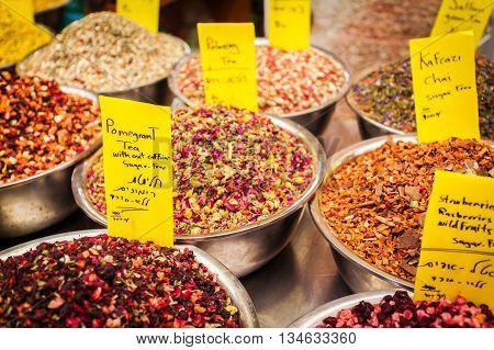 Different types of herbal tea with slices of dried fruit on the counter in Mahane Yehuda Market, Jerusalem, Israel. Cardamom tea, green tea, white tea, chocolate tea, Black tea, etc.