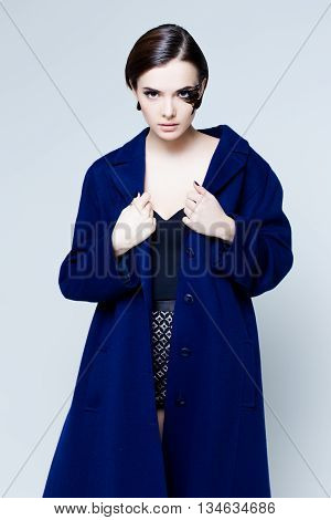 Young pretty woman face with false feather eyelashes fashion makeup  wearing blue coat poster