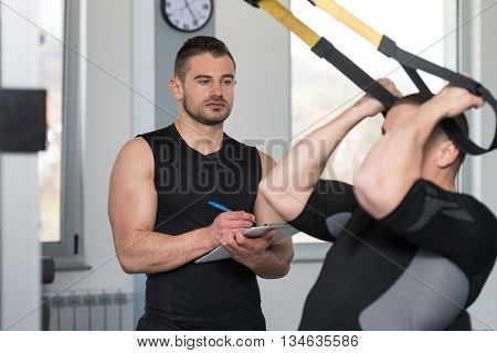 Trainer With Clipboard Man On Trx Fitness Straps