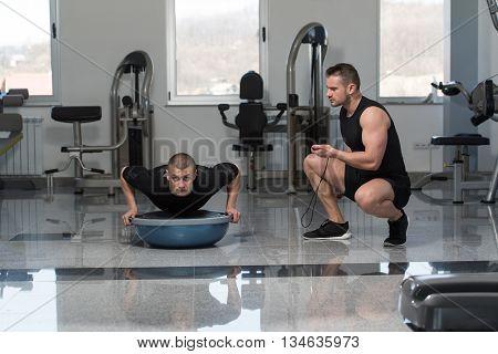 Personal Trainer Helping Man On Bosu Push Ups