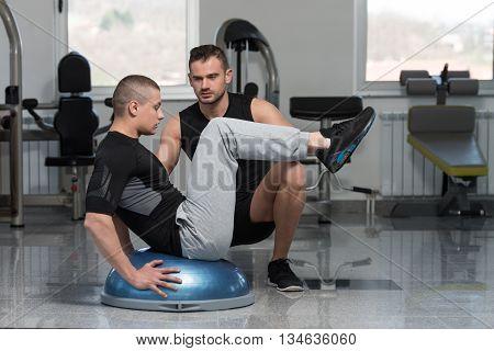Gym Coach Helping Man On Bosu Abs Exercise