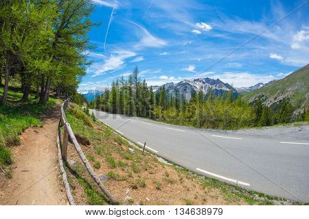 Paved Two Lane Road Crossing Mountains And Forest In Scenic Alpine Landscape And Moody Sky, Fisheye