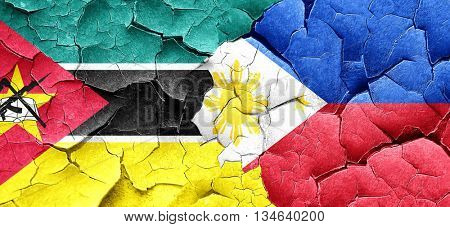 Mozambique flag with Philippines flag on a grunge cracked wall