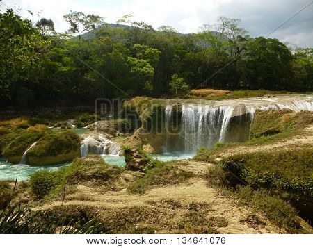 Turquoise, Azure, water flowing over multiple waterfalls with jungle background. Natural swimming pools with a jungle backdrop. Las Nubes, Chiapas, Mexico.