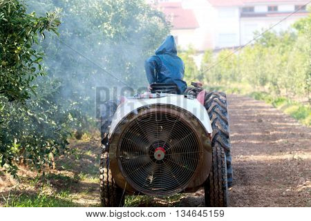 air blast sprayer with a chemical insecticide or fungicide in the orchard