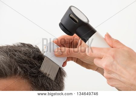Close-up Of Person Hand With Dermatoscope Examining Patient's Hair