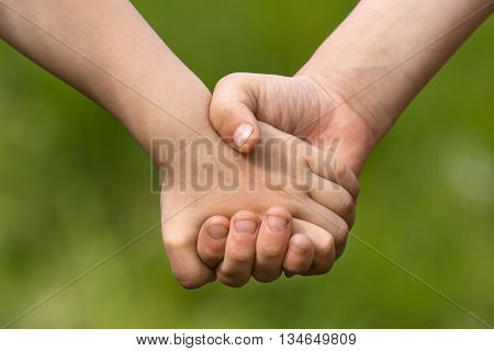two children holding hands each other on blurred background closeup