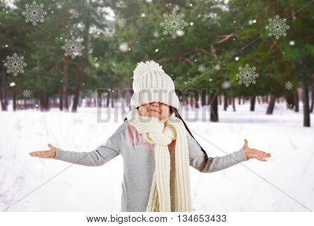 Confused little girl in a trendy knitted clothes and snowflakes on winter park landscape background
