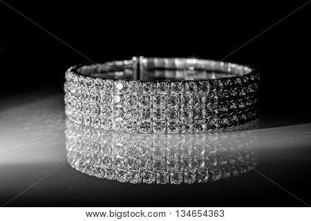 bracelet made of zirconium on a shiny glass surface
