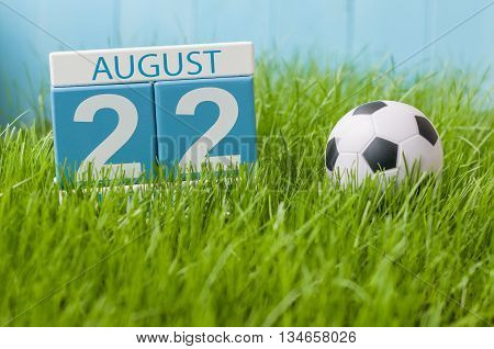 August 22nd. Image of august 22 wooden color calendar on green grass lawn background with soccer ball. Summer day. Empty space for text.