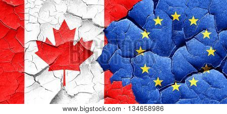 Canada flag with european union flag on a grunge cracked wall