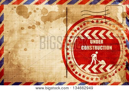 Under construction sign, red grunge stamp on an airmail backgrou