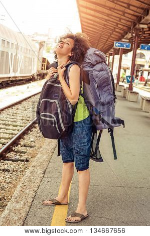 Beautiful tourist traveler standing with huge luggage at the railway station near the tracks