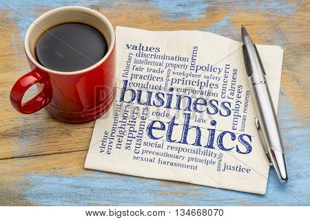 business ethics word cloud - handwriting on a napkin with cup of coffee