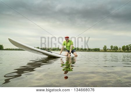senior male paddler on a paddleboard, lake in northern Colorado,  cloudy summer morning