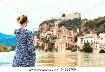 Woman traveller enjoying the view of the Miravet village and Ebro river. Province of Tarragona. Spain. Miravet is one of the most charming village in Catalonia