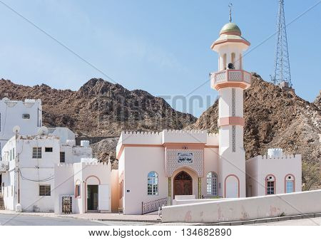 Small mosque in a typical Muscat neighbourhood with a rocky hill in the background in Muscat Oman.