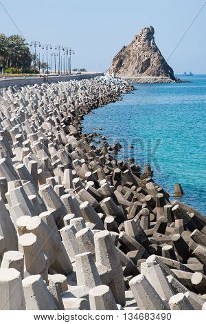 Road in Muscat Oman protected from erosion by concrete blocks with irregular shapes.