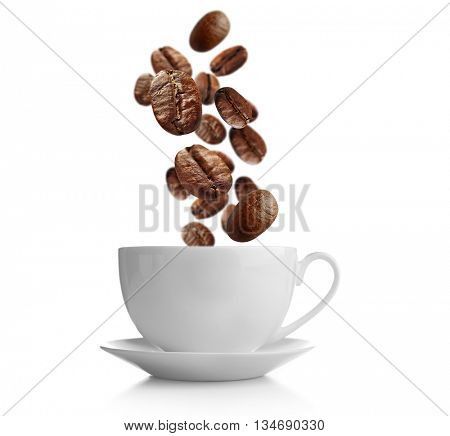 Ceramic cup with falling coffee beans and saucer isolated on white