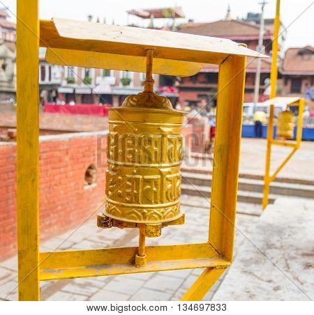 Yellow coloured Prayer Wheels placed at the Patan Durbar Square in KathmanduNepal.