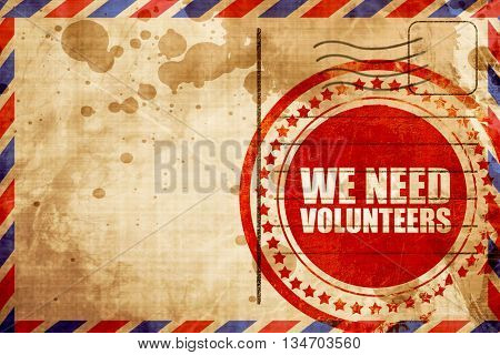 we need volunteers, red grunge stamp on an airmail background