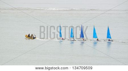 Felixstowe, Suffolk, England - June 11, 2016: Five small Colourful Sailing Dinghies being towed by a small inflatable power boat.