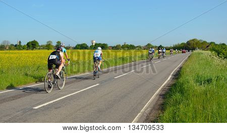Grafham, Cambridgeshire, England - May 22, 2016:  Triathletes on cycling stage racing on public road, moving away.