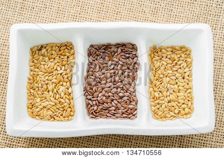 Difference of Golden linseeds and brown linseeds (flax seeds) in white cup on sack background.