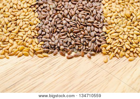 Difference of Golden linseeds and brown linseeds (flax seeds) on wooden background.