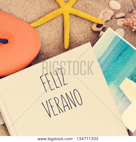 high-angle shot of a book with the text feliz verano, happy summer in Spanish written in its cover, an orange flip-flop, a starfish and a picture of the sea taken by myself, on the sand of a beach