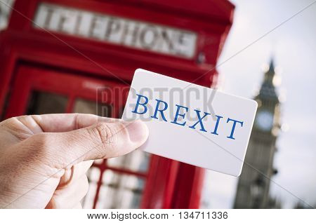 the hand of a young man showing a signboard with the text Brexit with a red telephone booth and the Big Ben in the background, in London, UK