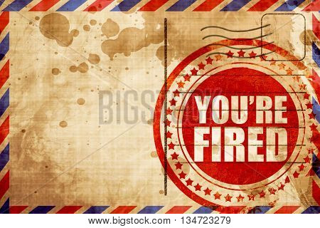 you're fired, red grunge stamp on an airmail background