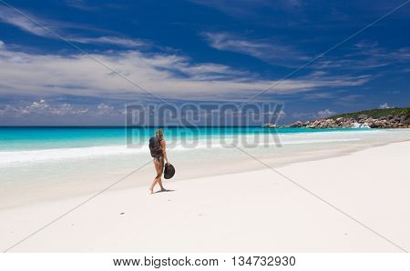 Blonde woman with backpack and hat, walks along a beach
