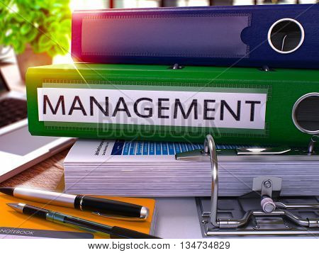 Green Ring Binder with Inscription Management on Background of Working Table with Office Supplies and Laptop. Management Business Concept on Blurred Background. 3D Render.
