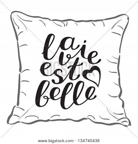 La vie est bell, life is beautiful in French. Brush hand lettering on a sample throw pillow. Great for pillow cases, posters, photo overlays, home decor and more.
