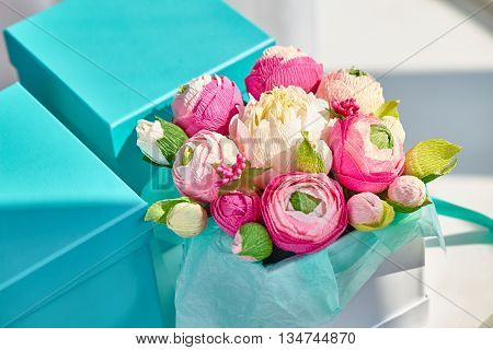 Bright bouquet of paper flowers in turquoise square box.