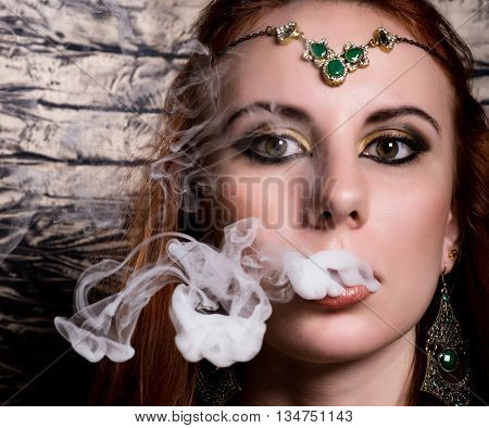 close-up portrait of a elegant young redhead woman, with oriental make-up and shawl over her head bright red lips, smokes a hookah, let the smoke out of his mouth.