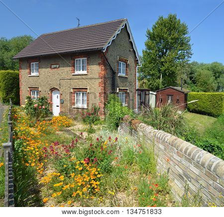 Offord Cluny, Cambridgeshire, England - June 09, 2016: English cottage with colourful cottage garden and wall.
