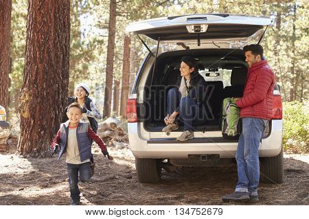 Parents watch kids and prepare for hike at the back of car