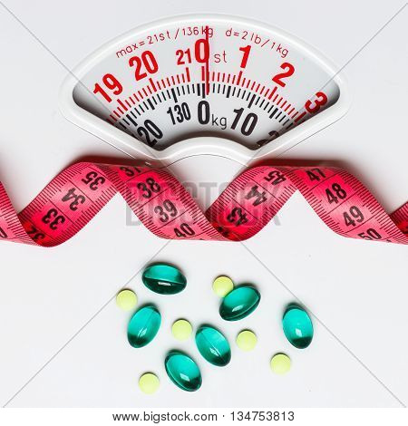 Healthy eating medicine health care food supplements and weight loss concept. Pills with measuring tape on white scales