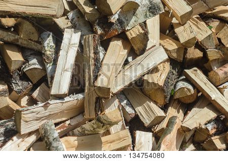 The background of firewood split firewood on a stack from different breeds of wood