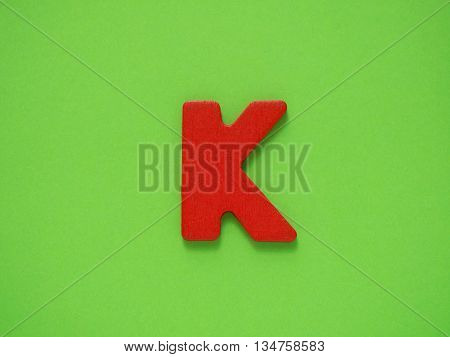 Capital letter K. Red letter K from wood on green background.