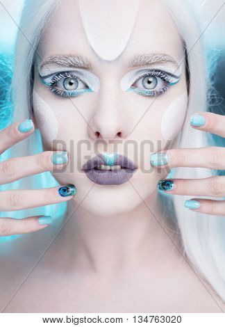 pretty woman with snow queen frosted makeup and light blue gel nails