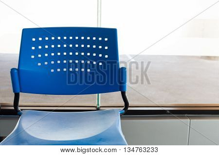 customer waiting area with rows of blue seats in office