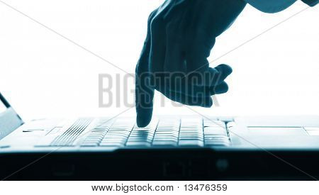 Close-up of  hand touching computer keys during work