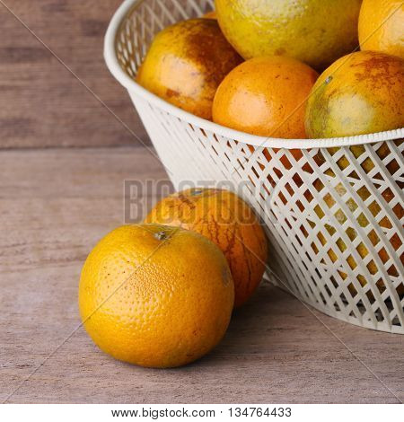 Orange Fruit In White Basket On Wood Table Background