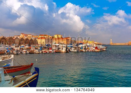 Chania Arsenals, the Venetian shipyards, and fishing boats in old harbour of Chania with Lighthouse in sunny and cloudy summer morning, Crete, Greece