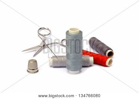 Needle, thimble, scissors, thread isolated on white background