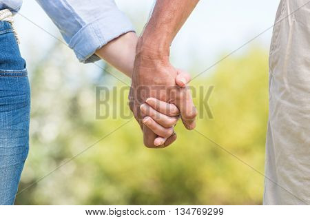 Closeup of couple holding hands outdoor. Romantic mature couple walking and holding hands. Close up hands of senior couple.