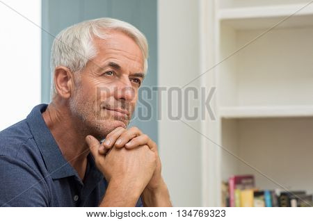 Portrait of thoughtful senior man at home. Pensive retired man smiling and looking up. Happy mature man thinking about his retirement.